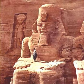 A man standing on the massive figure of Ramesses the Second at a temple in Abu-Simbel in Egypt, 186