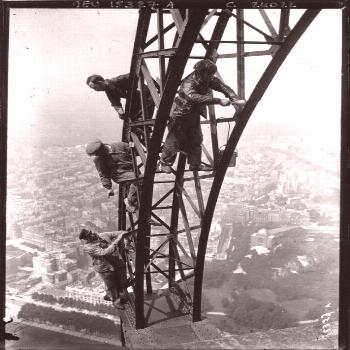 Unharnessed painters work amid the Eiffel Tower. Circa 1910.